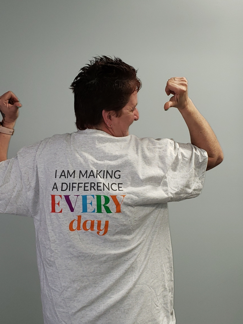 "A woman pointing to her tshirt which reads, ""I am making a difference every day""."
