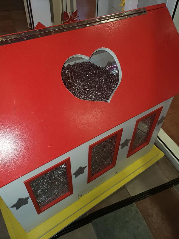 The donation box at the Ronald McDonald House. The lid is closed, but pull-tabs can be seen through the windows on the side of the box, and through the heart-shaped hole in the lid.