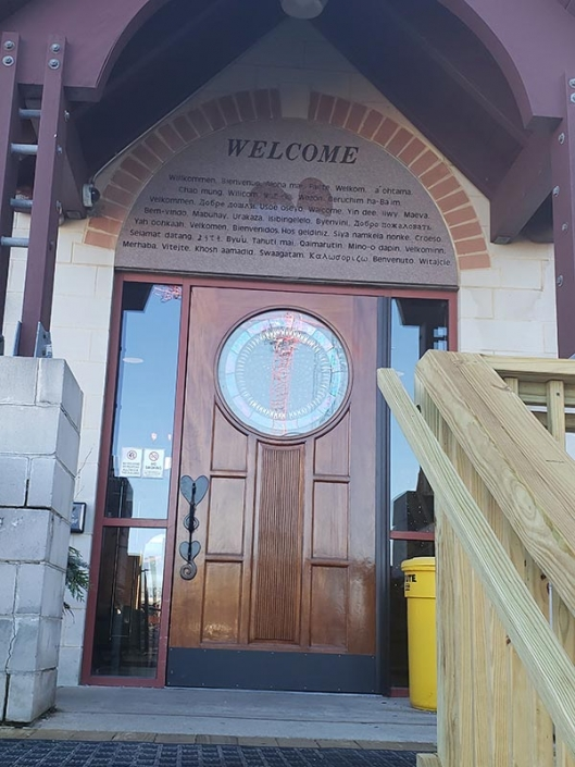 "The front door of the Ronald McDonald House. Above it is a slate that reads the word ""Welcome"" in several different languages."