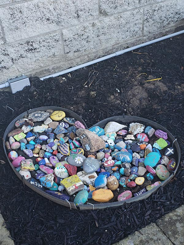 A heart-shaped bowl filled with colorful painted rocks.