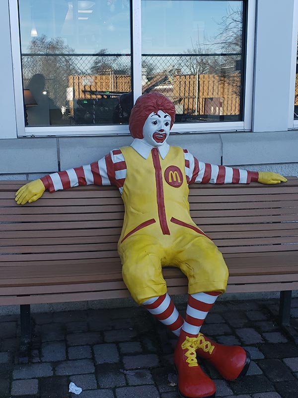 A statue of Ronald McDonald, a clown with red hair and a yellow outfit, sitting on a bench with his arms resting on the back of the bench.