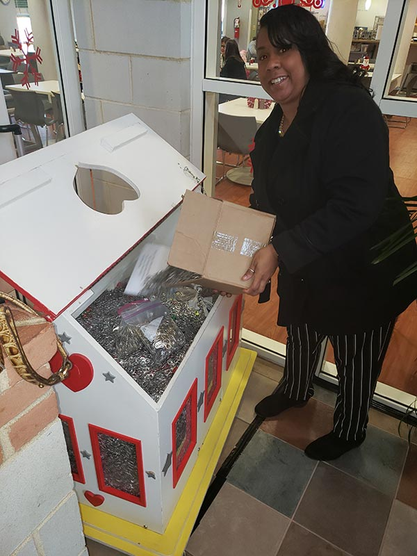 A woman pouring a box of pull-tabs from a can into a donation box at the Ronald McDonald House.