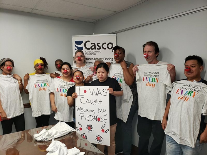 """A group of people wearing red noses. One of them is holding a sign that says """"I was caught wearing my red nose"""". The rest of them are holding t-shirts that say """"I am making a difference every day""""."""
