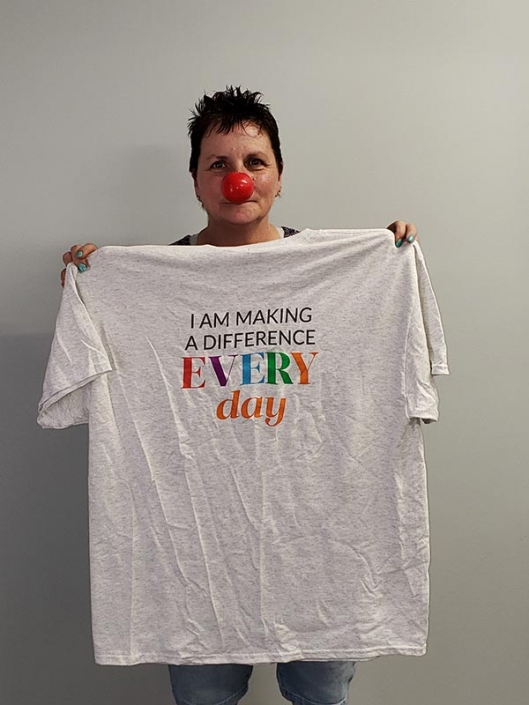 """A woman wearing a red nose and holding a shirt that says """"I am making a difference every day"""""""