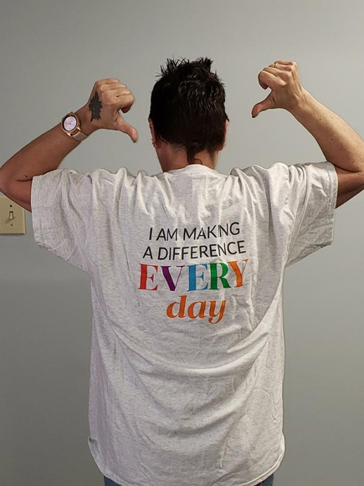 """A woman pointing to the words on her tshirt, which reads """"I am making a difference every day""""."""