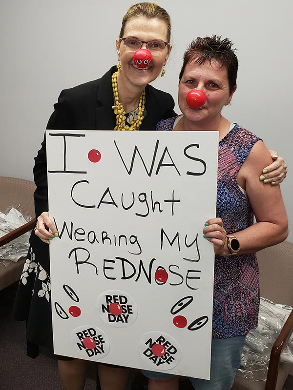 """Melissa Mangold (CEO of Casco) and Liz Boyer (Casco Employee). They are wearing red noses and holding a sign that says """"I was caught wearing my red nose""""."""
