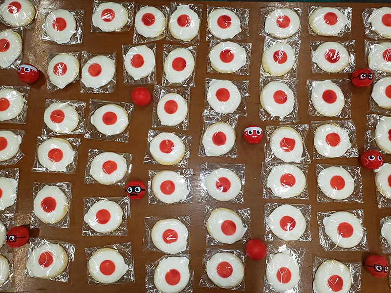 Cookies with white icing, and red icing in the middle to look like a red nose.