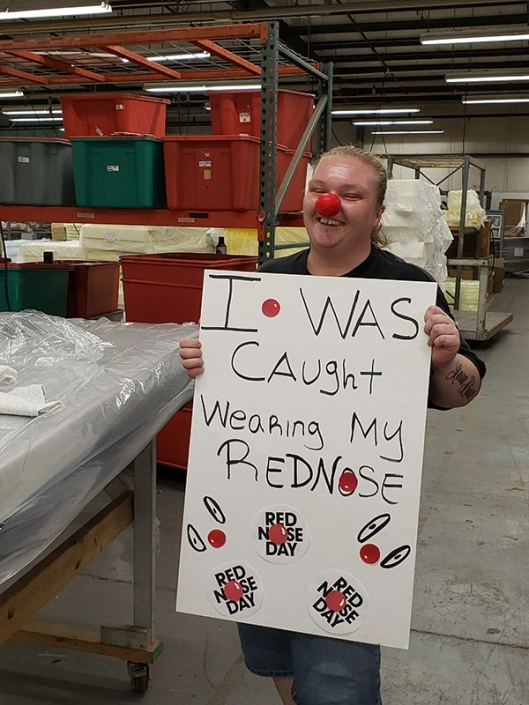 """A woman wearing a red nose. She is holding a sign that says """"I was caught wearing my red nose""""."""