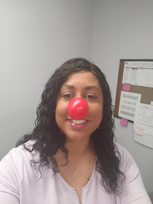 A woman wearing a red nose.