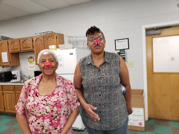 Two women wearing red noses.