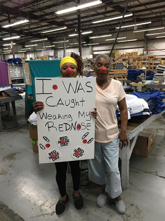 """Two women wearing red noses. One of them is holding a sign that says """"I was caught wearing my red nose""""."""
