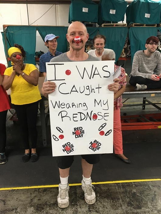 """A man wearing a red nose. He is holding a sign that says """"I was caught wearing my red nose""""."""